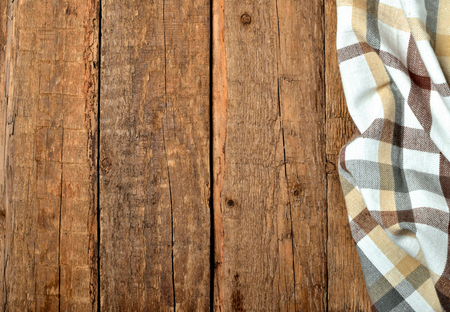 Brown white checkered tablecloth right frame on vintage wooden table background - view from above Imagens