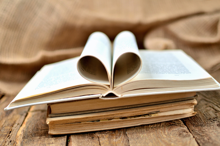 Old, vintage shabby open book with heart shaped pages