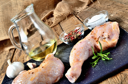 Raw spicy chicken legs ready for baking on a cutting board with a fresh rosemary, garlic, cumin, jug with oil, pepper and salt on a wooden table Imagens