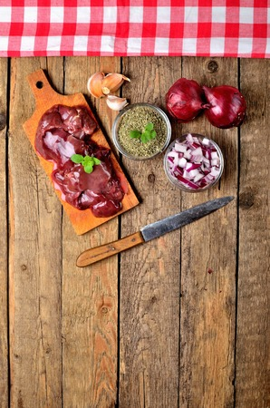 View from above of raw chicken liver on a wooden cutting board, fresh garlic, dried marjoram, oregano, onion, knife and red checkered tablecloth top frame - vertical photo Zdjęcie Seryjne