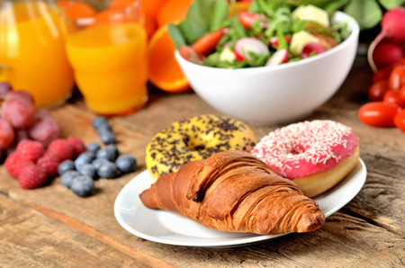 Donuts and croissant, orange juice, raspberry, blueberry and fresh salad - breakfast on wooden table