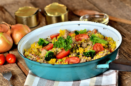 Tuna risotto with vegetables, tomatoes, broccoli and parsley in the old pan, onions, cans and oil in the background Imagens