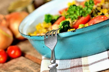 Close-up of fork and tuna risotto with vegetables, tomatoes, broccoli and parsley in the old pan, onions, cans and oil in the background Imagens