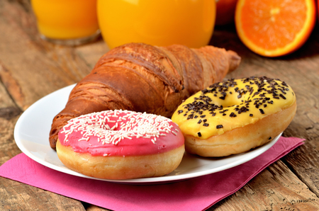 Sweet breakfast, croissant, donuts, oranges and orange juice on wooden table