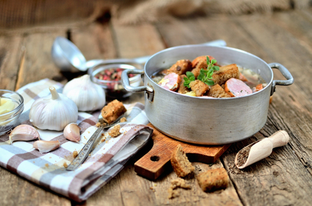 Garlic soup in an old saucepan, fresh garlic bulbs, cloves, colored pepper, wooden spoon, croutons, lable and a towel on a rustic wooden table Imagens