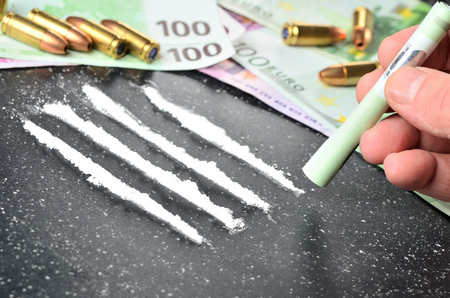 Man snorting cocaine line, euro banknotes and gun ammunition in background
