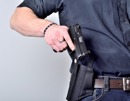 Close-up of man's hand pulling out a pistol gun from the holster on belt, blue jeans, black shirt