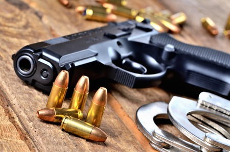 9mm pistol handgun, special police hollow-point expanding bullets and handcuffs on old wooden table - view to the barrel