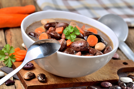 Close-up of bean soup with large beans , spoon, carrots, parsley and marjoram, towel and ladle in background