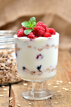 Greek yoghurt with oatmeal and fresh raspberries in a glass and mint leaves - vertical photo Imagens