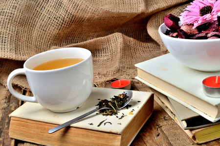 Mug of black tea and spoon with tea loose on an old, vintage shabby book, candle and dried flowers in background Imagens