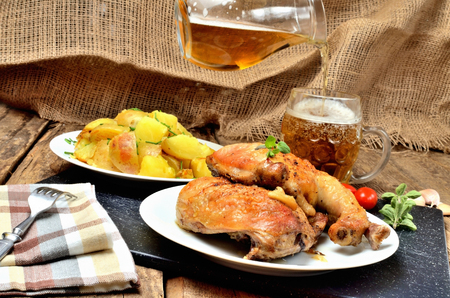 Grilled chicken legs on a plate, roasted potatoes and pouring cold beer into a glass, rosemary, tomatoes, oregano, salt, pepper and garlic on a wooden table Imagens