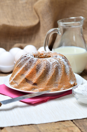 Homemade bundt cake sprinkled with sugar, milk and eggs in background, still life with marble cake on a white placemat and wooden table, vertical photo Imagens
