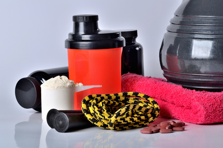 Close-up of protein powder shaker, jump rope, towel and kettlebell - fitness woman concept, isolated Imagens