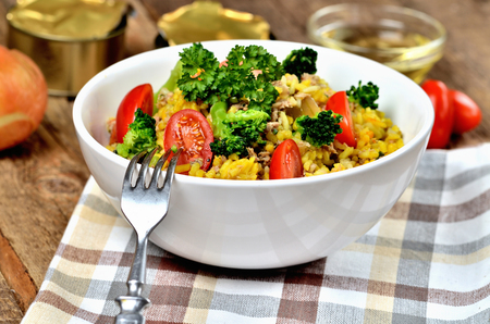 Close-up of fork and tuna risotto with vegetables, tomatoes, broccoli and parsley in the bowl, onions, cans and oil in the background
