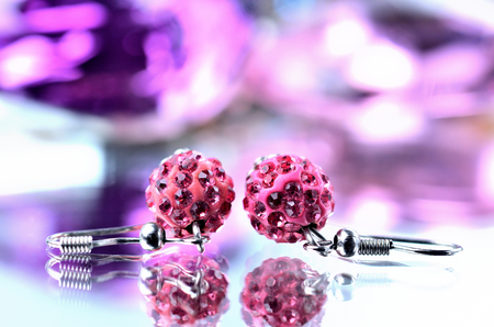 Red earrings with red diamonds jewels - reflection effect - colored backgrounds - purple Imagens - 115661570