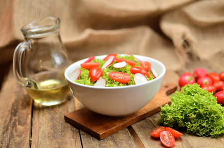 Green salad Lollo Biondo with tomatoes and radishes in a white bowl on wooden table, a pitcher of oil in the background Imagens - 120033788