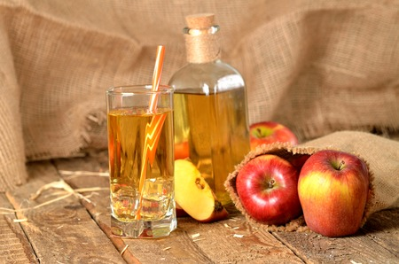 Juice from fresh apples, straw, ice and bottle in background on wooden boards