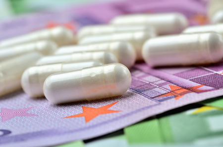 Close-up of pills on euro banknotes - concept of healthcare and finance Imagens
