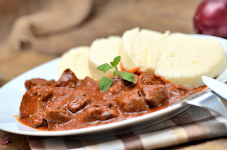 Close-up of pork goulash meat with dumplings on white plate, cutlery, garlic, onion, pepper, tablecloth in the background - typical Czech food