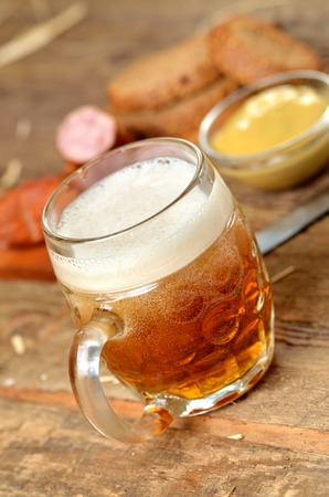 Cold glass of beer, sausage, mustard and bread in the background - vertical photo