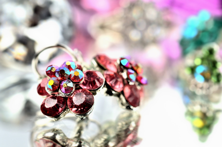 Close-up of red flower shaped earrings with red diamonds and ring jewelery - reflection effect - colored backgrounds - purple - warm color balance Imagens - 120033792