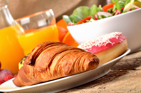 Detail of croissant, orange juice and fresh salad - breakfast on wooden table Imagens