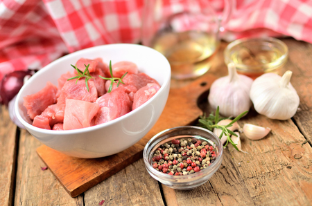 Raw pork meal diced in a bowl, garlic, half of onion, pepper, jug with oil and checkered red tablecloth in the background