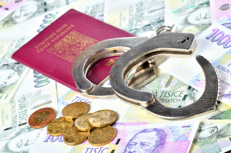Czech republic passport, coins and police handcuffs on banknotes - international arrest warrant concept