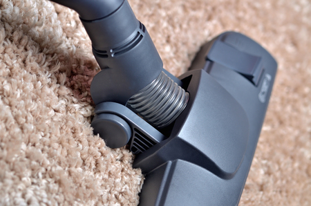 Close-up of head of vacuum cleaner on shaggy carpet - close-up of noozle