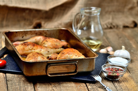 Golden roasted chicken legs in a baking pan, pepper, salt, garlic, cherry tomatoes, fork and jug with oil in the background Imagens - 120034086