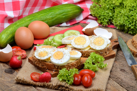 Wholemeal bread with butter, hard-boiled eggs, fresh radishes, tomatoes, salad and cucumbers in background