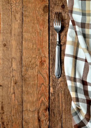 Checkered tablecloth right frame and fork on vintage wooden table background - view from above - vertical photo Imagens