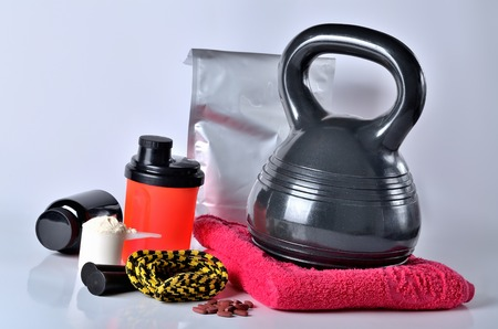 Protein powder, vitamines, shaker protein pack, jump rope, towel and kettlebell - fitness concept, isolated Imagens - 123631423