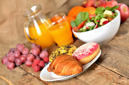 Croissant and donuts, orange juice and fresh salad - breakfast on wooden table Imagens