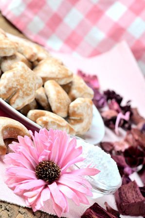 Close-up of gingerbreads, romantic pink flower and a checkered towel in background
