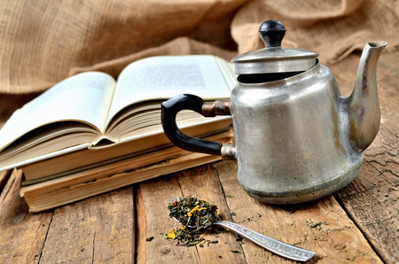 Old, vintage open book, old teapot and spoon with tea loose