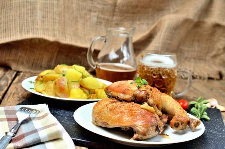 Golden grilled chicken legs on a plate, roasted potatoes and jug of cold beer, rosemary, tomatoes, oregano, salt, pepper and garlic on a wooden table Imagens - 123631435
