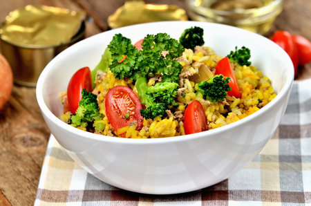 Close-up of tuna risotto with vegetables, tomatoes, broccoli and parsley in the bowl, onions, cans and oil in the background Imagens - 123631432