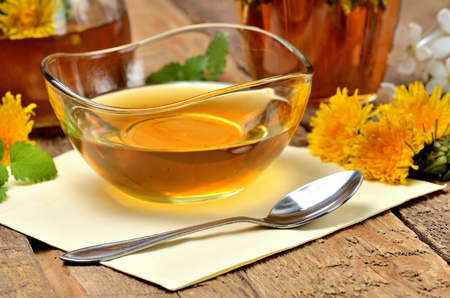 Close-up of dandelion honey in a glass bowl and dandelion head around, jar and herbal tea in background