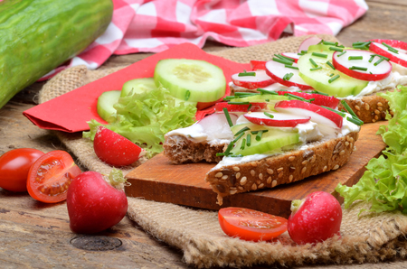 Wholemeal grain bread with curd cheese, fresh radish, cucumber and tomatoes on a wooden cutting board - concept of healthy fitness breakfast or snack, salad and whole cucumber in background