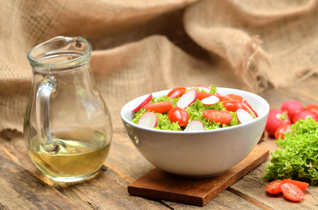 Green salad Lollo Biondo with tomatoes and radishes in a white bowl on wooden table, a pitcher of oil in the background Imagens - 123633984