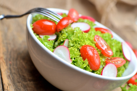Close-up of green salad Lollo Biondo with tomatoes and radishes in a white bowl with fork on wooden table