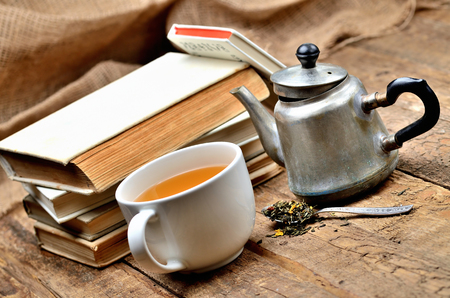 Stack of vintage books, cup of black tea, old teapot and spoon with tea loose