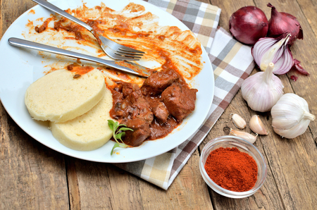 Eating pork goulash meat with dumplings on white plate, cutlery, garlic, onion, pepper, tablecloth in the background - typical Czech food