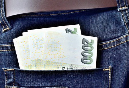 Czech banknotes money in the back pocket of jeans with belt, thousand, two thousand Czech crowns Imagens - 123633994
