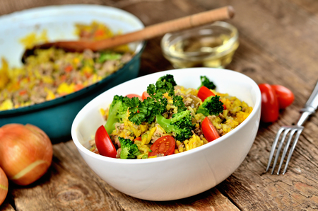 Bowl with tuna risotto with vegetables, tomatoes, broccoli and parsley, onions and oil in the background Imagens