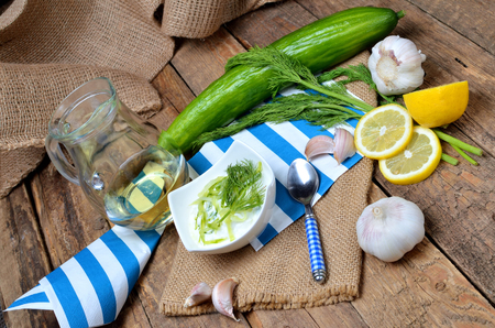 Tzatziki - traditional Greek dressing or dip sauce, garlic, lemon, dill, cucumber, jug with oil, blue spoon and decoration in background Imagens