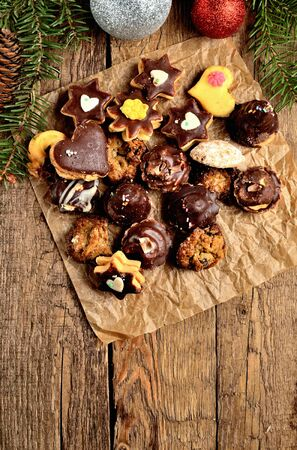 View from above of christmas sweets with different types of candy on baking paper and Christmas decorations in background vertical photo Imagens - 125369893
