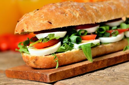 Large baguette sandwich cut in half filled with egg, arugula salad, tomatoes and radish in background orange juice, spring onion on wooden cutting board Imagens - 125369896